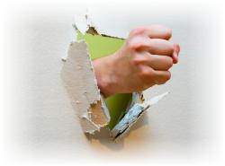 Puño rompiendo una pared