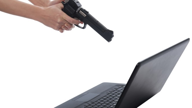 Women's hands with a gun takes aim at Laptop Monitor