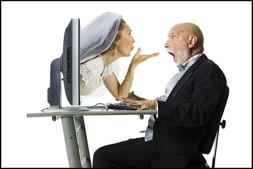 Profile of a senior woman blowing a kiss through a computer monitor to her groom