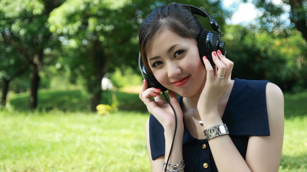 mujer asiática escuchando música