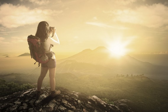 Female backpacker taking photo at mountain