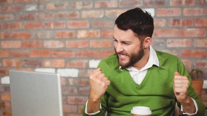 Excited businessman clenching fist while looking at laptop in cr
