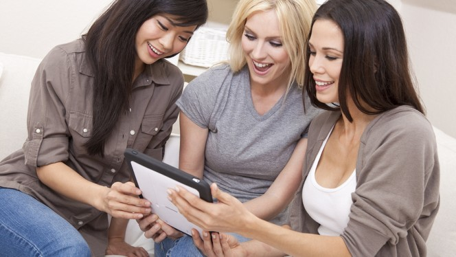 Three beautiful young women friends at home using tablet compute