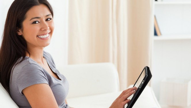 smiling woman sitting on sofa with tablet looking into camera in