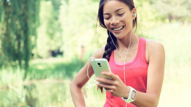 Happy young fit woman using cell phone while listening to music