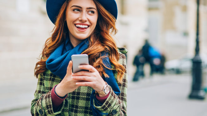Attractive woman with a phone in the city using FreedomPop